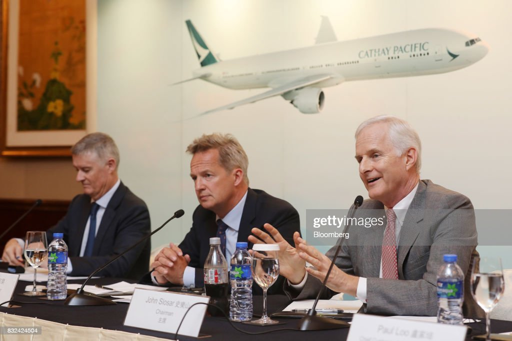 John Slosar, chairman of Cathay Pacific Airways Ltd., right, speaks as Rupert Hogg, chief executive officer, center, looks on during a news conference in Hong Kong, China, on Wednesday, Aug. 16, 2017. Cathay Pacific is slipping in its efforts to get passengers to pay more for its premium services in a test for new Chief Executive Officer Hogg as the company reported back-to-back losses. Photographer: Paul Yeung/Bloomberg via Getty Images