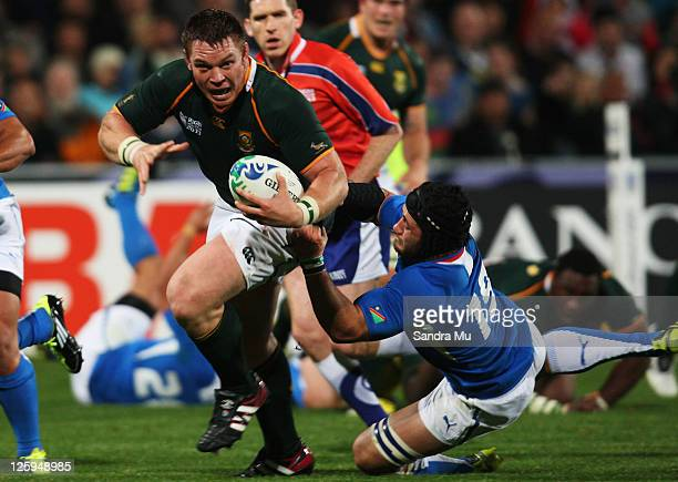 John Smit of South Africa evades the tackle of Rohan Kitshoff of Namibia during the IRB 2011 Rugby World Cup Pool B match between South Africa and...