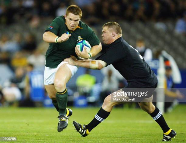 John Smit of South Africa is tackled by Greg Somerville of New Zealand during the Rugby World Cup Quarter Final 1 match between New Zealand and South...