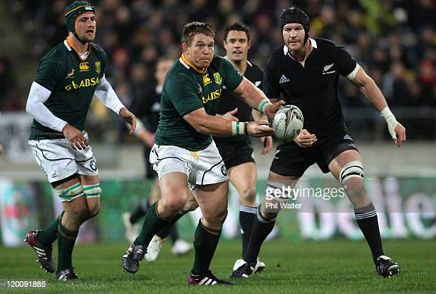 John Smit of the Springboks passes the ball during the TriNations match between the New Zealand All Blacks and the South African Springboks at...