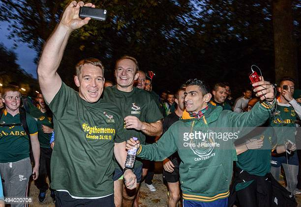 John Smit takes a photo of Captain Francois Pienaar as he leads the public and the 1995 South African Rugby World Cup winning squad on a run through...