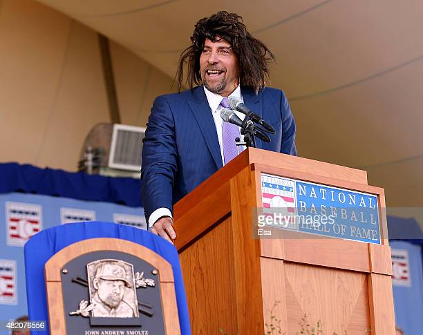 John Smoltz tries to relive his early days with hair as he speaks wearing a wig during the Hall of Fame Induction Ceremony at National Baseball Hall...