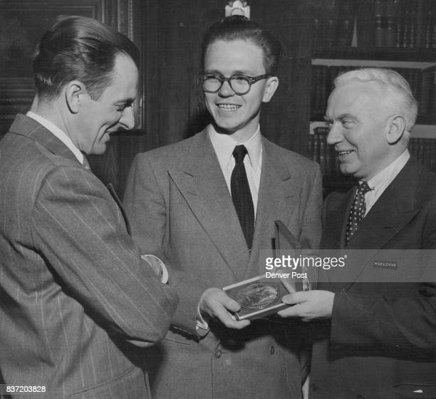 John Somerville displays the gold honor award he received Saturday for his cartoon entitled 'Trying to Keep It From Getting Around' the medal was...
