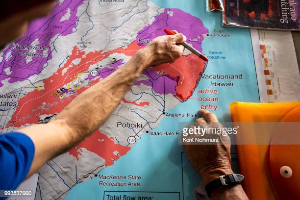 John Stallman from Orchidland Hilo HI points to areas where lava has expanded the coast of Hawaii Island while talking with Kalapana resident Jerry...