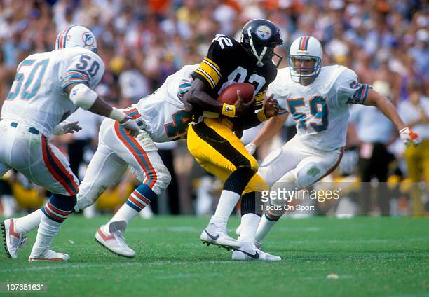 John Stallworth of the Pittsburgh Steelers is grabbed from behind by William Judson of the Miami Dolphins during an NFL football game at The Orange...