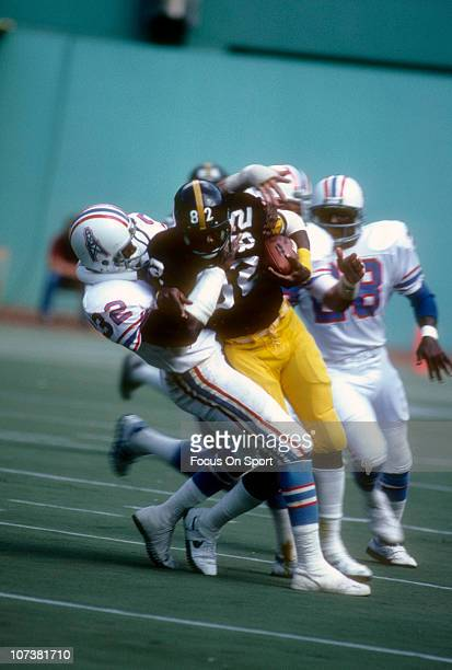 John Stallworth of the Pittsburgh Steelers is tackled by Vernon Perry of the Houston Oilers during an NFL football game at Three Rivers Stadium circa...