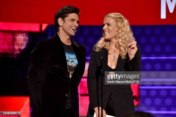 John Stamos and Busy Philipps speak onstage during the 2018 American Music Awards at Microsoft Theater on October 9 2018 in Los Angeles California