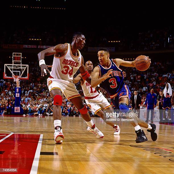 John Starks of the New York Knicks dribbles against Hakeem Olajuwon of the Houston Rockets during Game Seven of the 1994 NBA Finals at the Summit on...