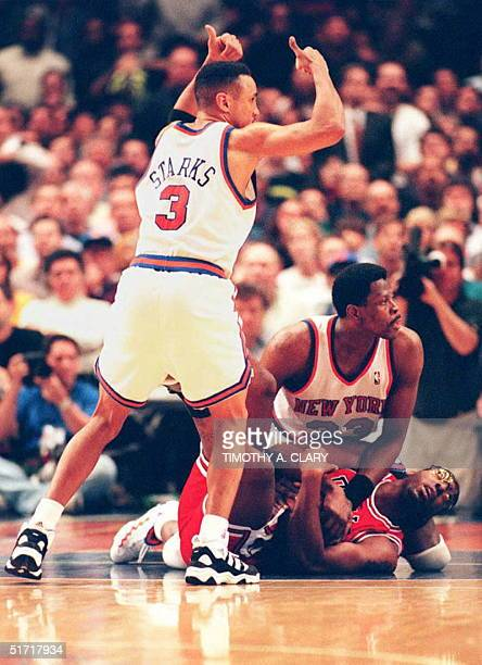 John Starks of the New York Knicks signals for a jump ball as his teammate Patrick Ewing and John Salley of the Chicago Bulls fight for the ball...