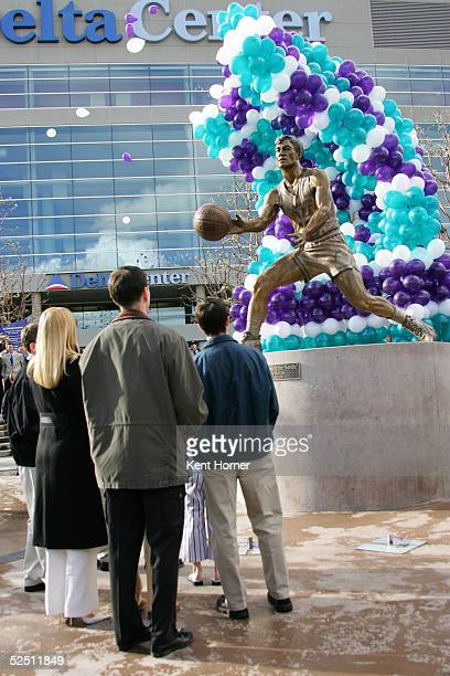 John Stockton his wife Nada and son watch as balloons reveal his 9foot bronze statue during the unveiling March 30 2005 in front of the Delta Center...