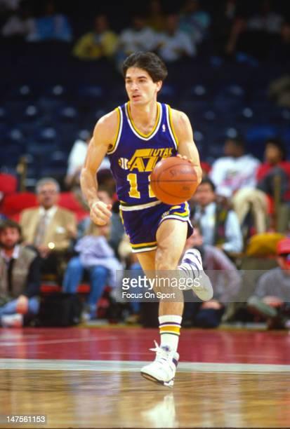 John Stockton of the Utah Jazz dribble the ball up court against the Washington Bullets during an NBA basketball game circa 1988 at the Capital...