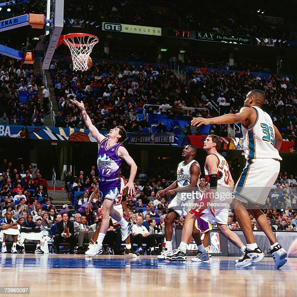 John Stockton of the Western Conference shotos against Grant Hill of the Eastern Conference during the 1997 AllStar Game on February 9 1997 at Gund...