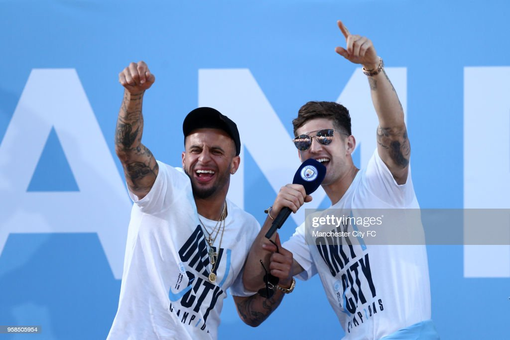 John Stones (R) and Kyle Walker (L) of Manchester City acknowledges the fans from the stage during the Manchester City Trophy Parade on May 14, 2018 in Manchester, England.