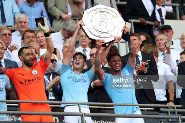 John Stones and Kyle Walker of Manchester City lift the FA Community Shield Trophy following their sides victory in the FA Community Shield between...