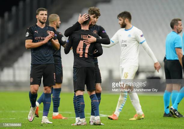 John Stones and Phil Foden of Manchester City embrace after the UEFA Champions League Group C stage match between Olympique de Marseille and...