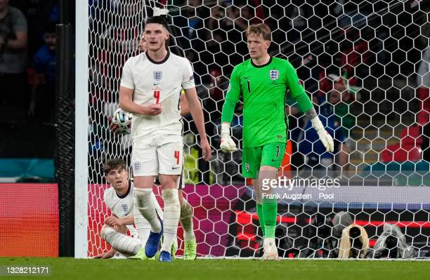 John Stones, Declan Rice and Jordan Pickford of England look dejected after conceding their side's first goal scored by Leonardo Bonucci of Italy...