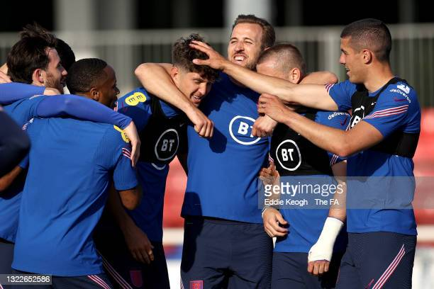 John Stones, Harry Kane, Luke Shaw and Conor Coady of England and teammates huddle during a training session at St George's Park on June 08, 2021 in...