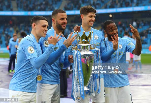 John Stones, Kyle Walker, Raheem Sterling and Phil Foden of Manchester City celebrate with the Premier League trophy during the Premier League match...