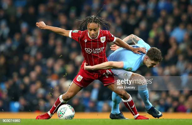 John Stones of Manchester City and Bobby Reid of Bristol City tussle for the ball during the Carabao Cup SemiFinal First Leg match between Manchester...
