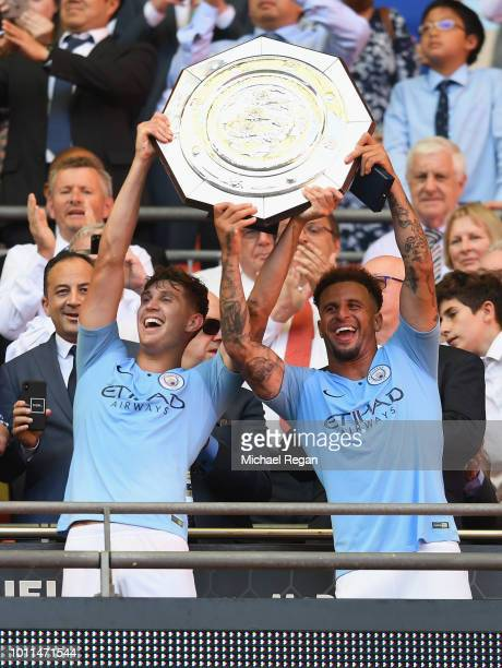 John Stones of Manchester City and Kyle Walker of Manchester City celebrate with the Community Shield trophy during the FA Community Shield between...