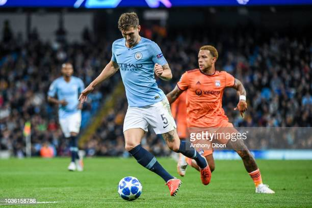 John Stones of Manchester City and Memphis Depay of Lyon during the Champions League match between Manchester City and Lyon at Etihad Stadium on...