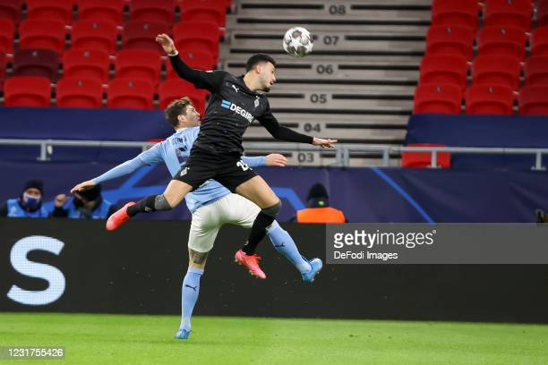 John Stones of Manchester City and Ramy Bensebaini of Borussia Moenchengladbach battle for the ball during the UEFA Champions League Round of 16...