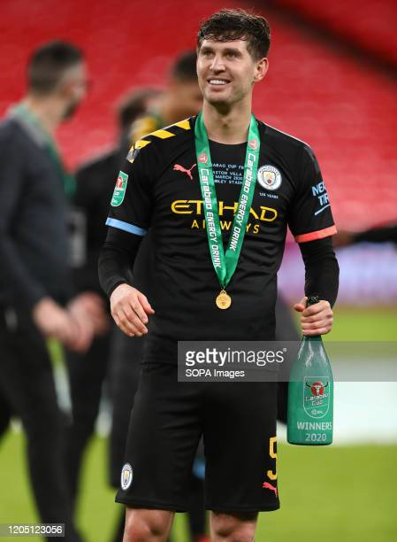 John Stones of Manchester City celebrates with his winners medal and champagne after the Carabao Cup Final match between Aston Villa and Manchester...