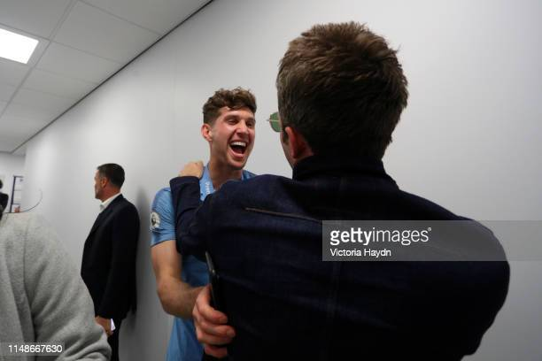 John Stones of Manchester City celebrates with Noel Gallagher in the Manchester City dressing room following the Premier League match between...