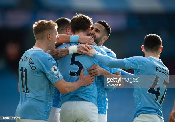 John Stones of Manchester City celebrates with Riyad Mahrez and team mates after scoring the second goal during the Premier League match between...
