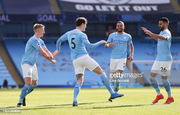 John Stones of Manchester City celebrates with team mates Kyle Walker, Riyad Mahrez and Oleksandr Zinchenko after scoring their side's second goal...