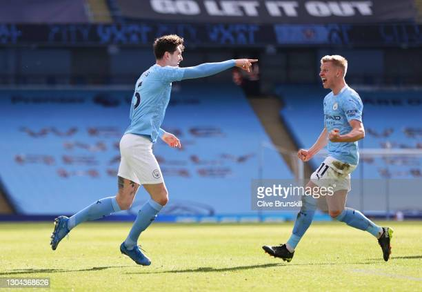 John Stones of Manchester City celebrates with teammate Oleksandr Zinchenko after scoring his team's first goal during the Premier League match...
