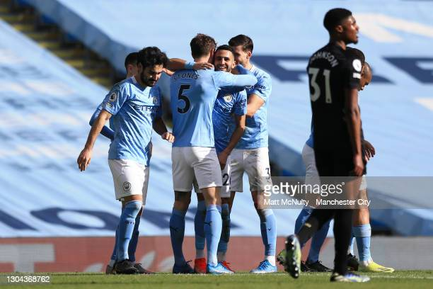 John Stones of Manchester City celebrates with teammate Riyad Mahrez after scoring his team's second goal during the Premier League match between...