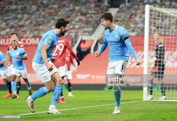 John Stones of Manchester City celebrates with teammate Ruben Dias after scoring his teams first goal during the Carabao Cup Semi Final match between...