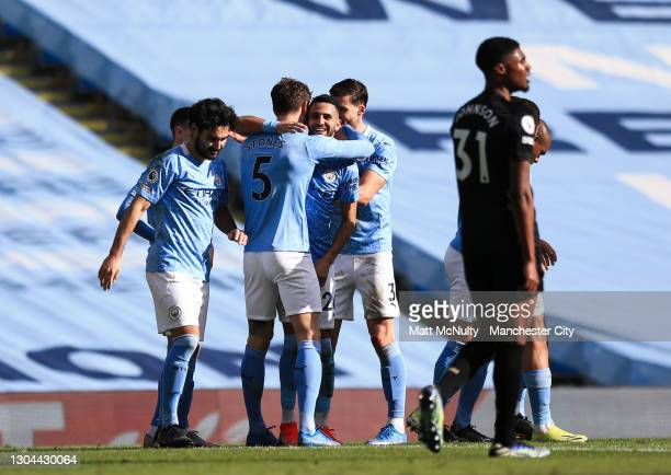 John Stones of Manchester City celebrates with teammates after scoring his teams second goal during the Premier League match between Manchester City...