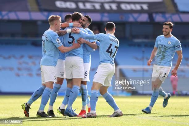 John Stones of Manchester City celebrates with teammates Oleksandr Zinchenko, Riyad Mahrez, Phil Foden and Ruben Dias after scoring his team's second...