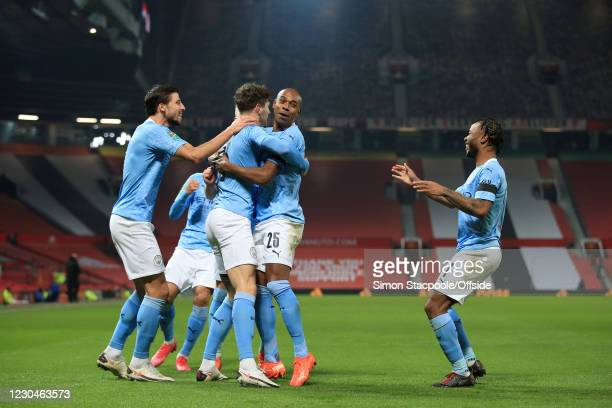John Stones of Manchester City celebrates with teammates Ruben Dias of Manchester City , Fernandinho of Manchester City and Raheem Sterling of...