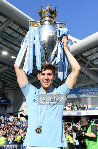 John Stones of Manchester City celebrates with the Premier League Trophy after winning the title following the Premier League match between Brighton...