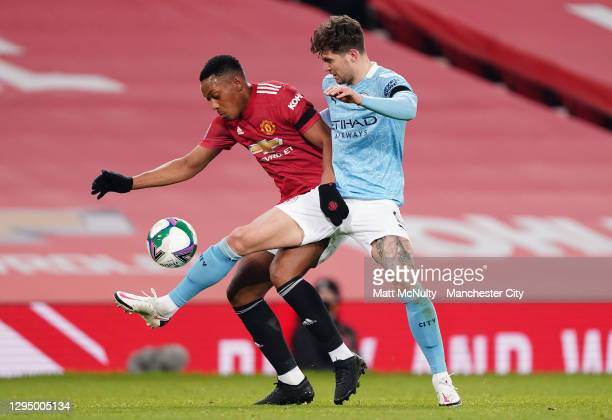 John Stones of Manchester City challenges Anthony Martial of Manchester United during the Carabao Cup Semi Final match between Manchester United and...