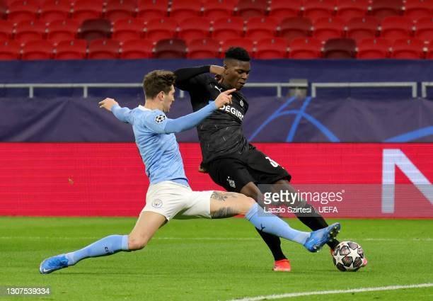 John Stones of Manchester City challenges Breel Embolo during the UEFA Champions League Round of 16 match between Manchester City and Borussia...