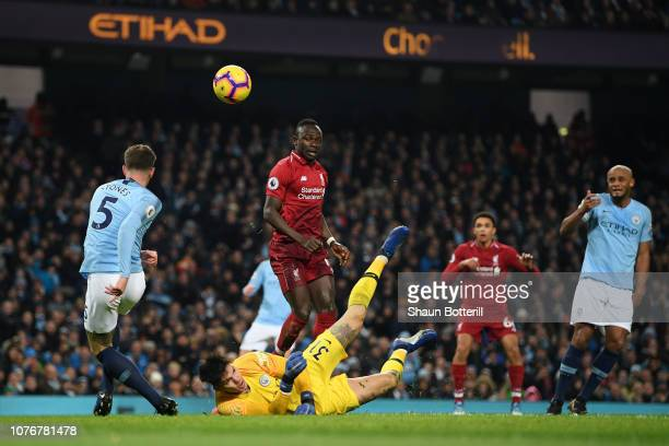 John Stones of Manchester City clears the ball as Ederson of Manchester City saves from Sadio Mane of Liverpool during the Premier League match...