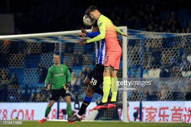 John Stones of Manchester City contests for a header with Alessio Da Cruz of Sheffield Wednesday during the FA Cup Fifth Round match between...