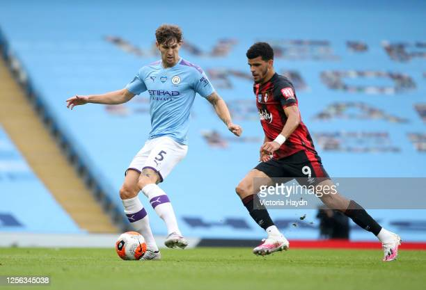 John Stones of Manchester City controls the ball as Dominic Solanke of AFC Bournemouth looks on during the Premier League match between Manchester...