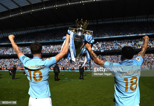 John Stones of Manchester City holds the Premier League Trophy with Kyle Walker of Manchester City towards the fans during the Premier League match...