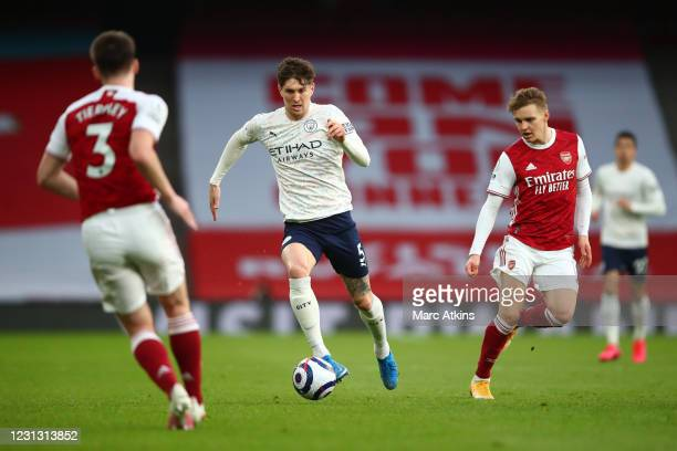 John Stones of Manchester City in action with Martin Odegaard of Arsenal during the Premier League match between Arsenal and Manchester City at...