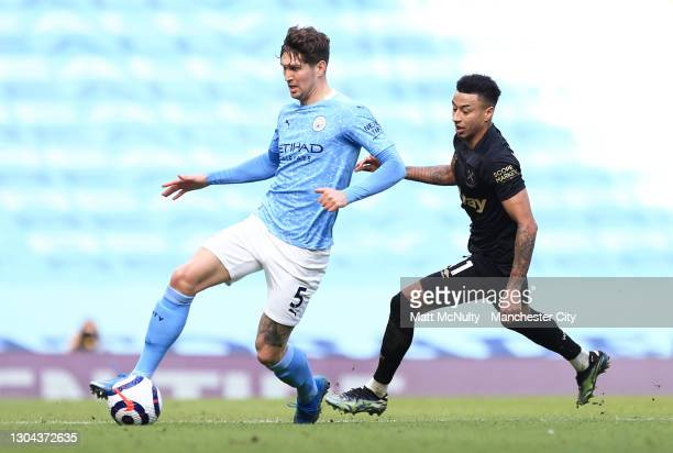 John Stones of Manchester City is challenged by Jesse Lingard of West Ham United during the Premier League match between Manchester City and West Ham...