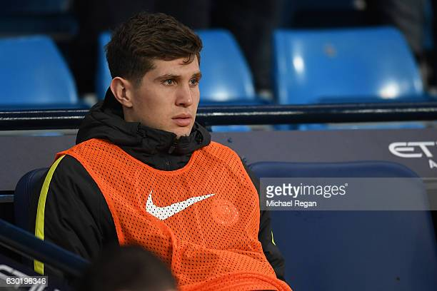 John Stones of Manchester City looks on from his seat on the Manchester City bench during the Premier League match between Manchester City and...