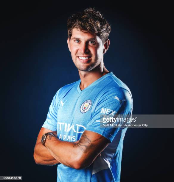 John Stones of Manchester City poses for a portrait after signing a contract extension at Manchester City Football Academy on August 10, 2021 in...
