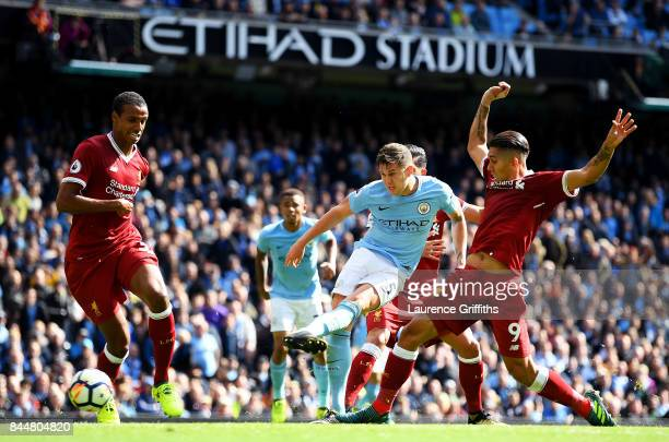 John Stones of Manchester City shoots as Roberto Firmino of Liverpool attempts to block during the Premier League match between Manchester City and...