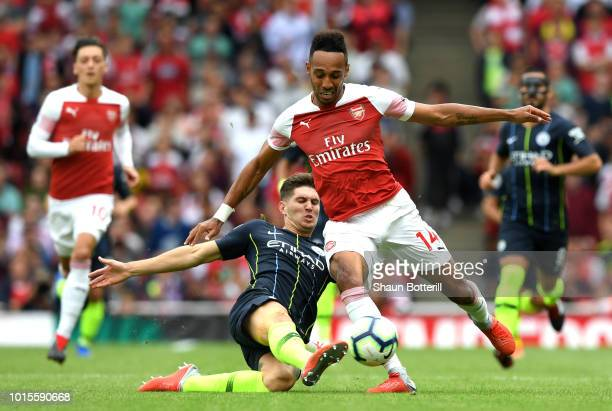 John Stones of Manchester City tackles PierreEmerick Aubameyang of Arsenal during the Premier League match between Arsenal FC and Manchester City at...