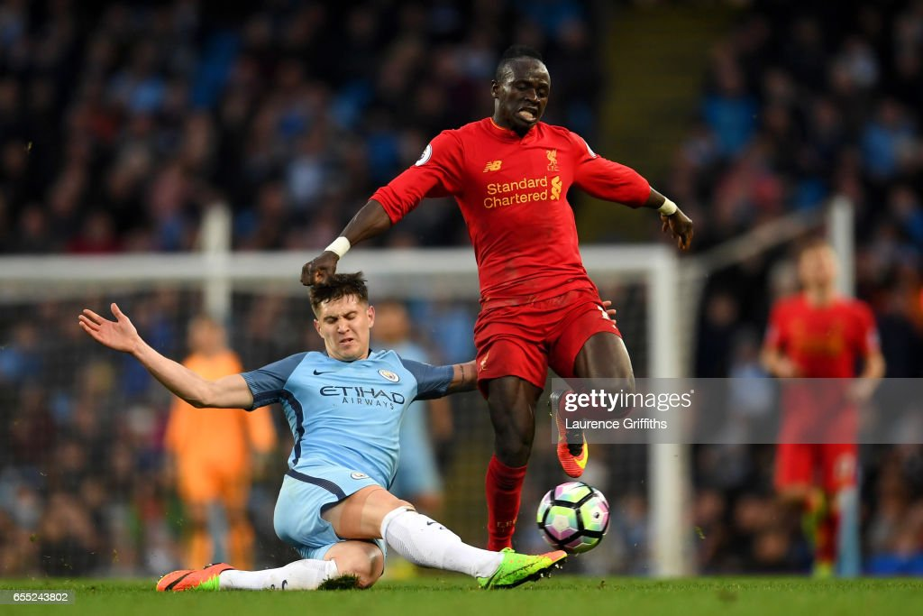 John Stones of Manchester City (L) tackles Sadio Mane of Liverpool (R) during the Premier League match between Manchester City and Liverpool at Etihad Stadium on March 19, 2017 in Manchester, England.